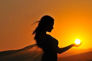 What Inspires You to Create a Breakthrough Mindset? image woman holding the sun in the palm of her hand
