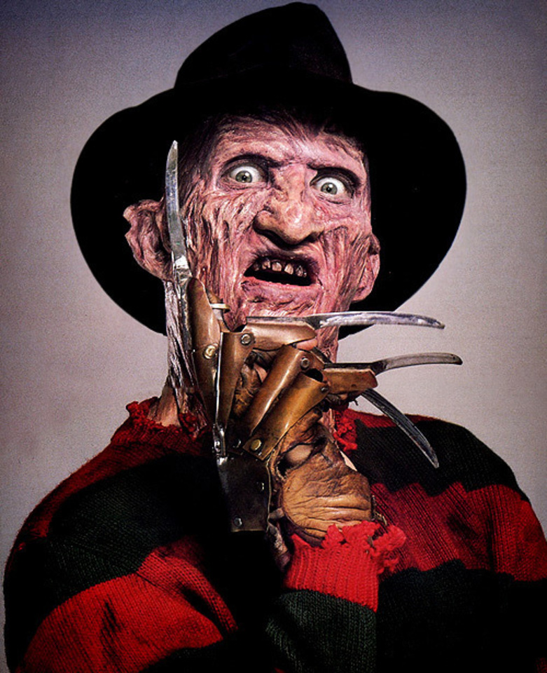 Freddy Krueger with severe facial scarring and a prosthetic hand that has blades as fingers.